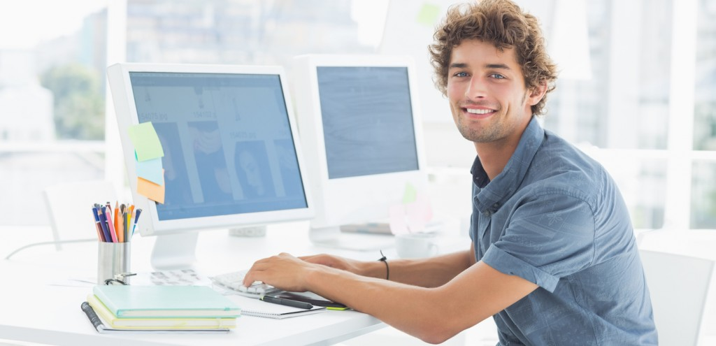 Side view portrait of a smiling casual young man using computer in a bright office